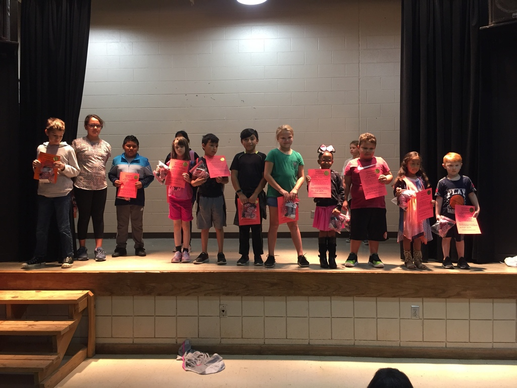 Students holding student of the month certificates.